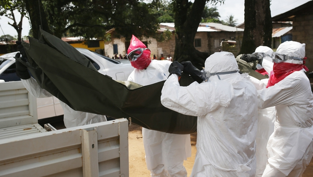 A burial team from the Liberian health department removes the body of a woman suspected of dying of Ebola