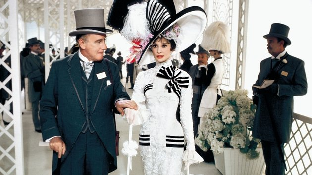 Eliza is escorted by Colonel Pickering, played by Wilfrid Hyde-White, on a day at the races at Ascot