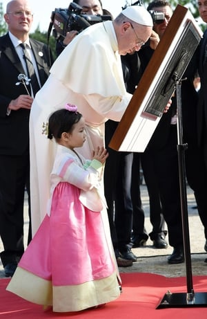 The pontiff signs a guest book after visiting the shrine of Solmoe, the house of Saint Andrew Kim Taegon
