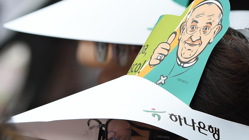 The image of Pope Francis is seen on a sun hat worn by a woman attending mass in Daejeon
