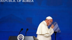 Francis takes off his glasses after delivering his speech during a news conference at the presidential Blue House in Seoul