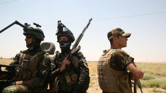 Iraqi soldiers keep watch  on the main highway which links the Iraqi capital to the borders with Syria