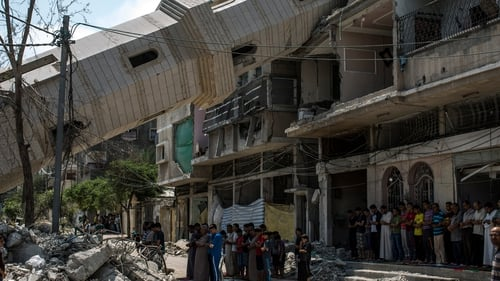 Palestinians attend Friday noon prayers in the shadow of a toppled minaret at Al-Susi Mosque in Gaza City