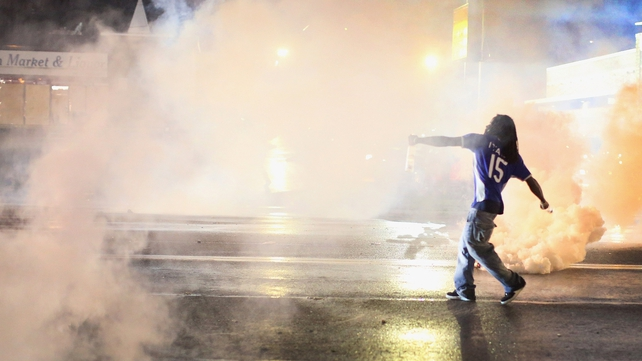 A demonstrator throws a grenade back at police after a brief clash in Ferguson, Missouri