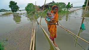 A woman crosses a make-shift bamboo bridge along with her child in the flood-affected Morigaon district of Assam state in India