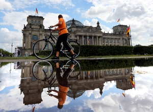 A woman wheels her bike past the Reichstag building in Germany