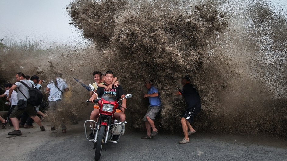 Tide spectators react to a high wave hitting the bank of Qiantang River in Zhejiang province, China