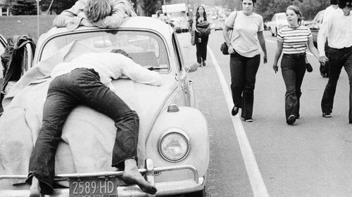 two festival-goers take a rest on a VW Beetle at Woodstock in 1969