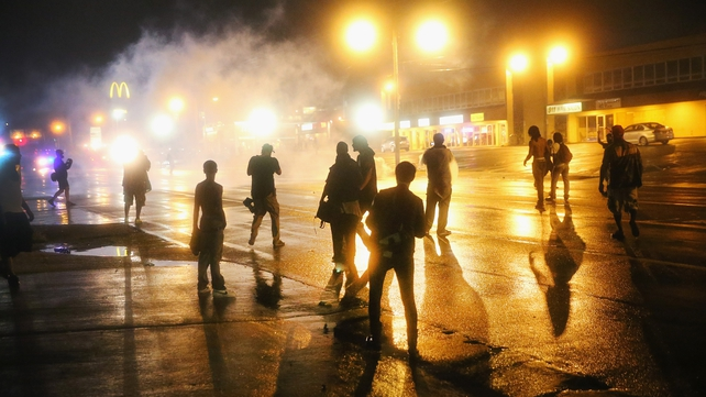 People on the streets of Ferguson after the midnight curfew, its has been extended for a second night