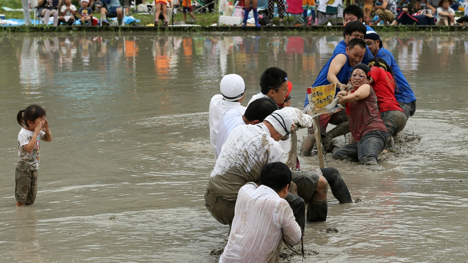 Festival-goers play tug-of-war in the mud during a village mud festival in Himeji, Japan