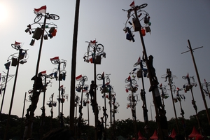 Indonesians silhouetted against the sun participate in a palm tree climbing competition in Jakarta