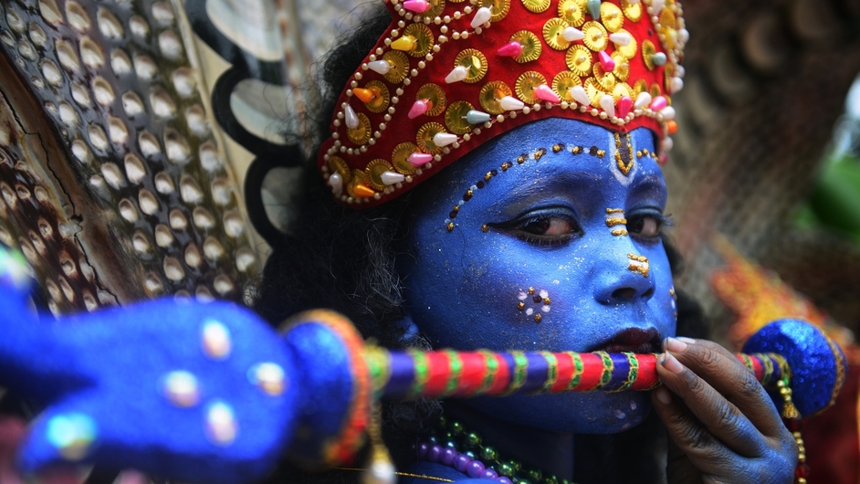 A Bangladeshi youth dressed as the Hindu god Lord Krishna takes part in a procession in Dhaka
