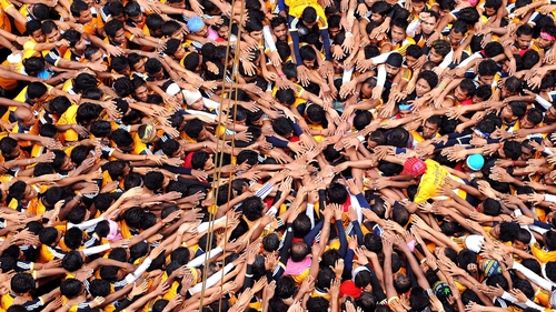 Indian Hindu devotees gesture before attempting to form a human pyramid during celebrations for the Janmashtami festival in Mumbai