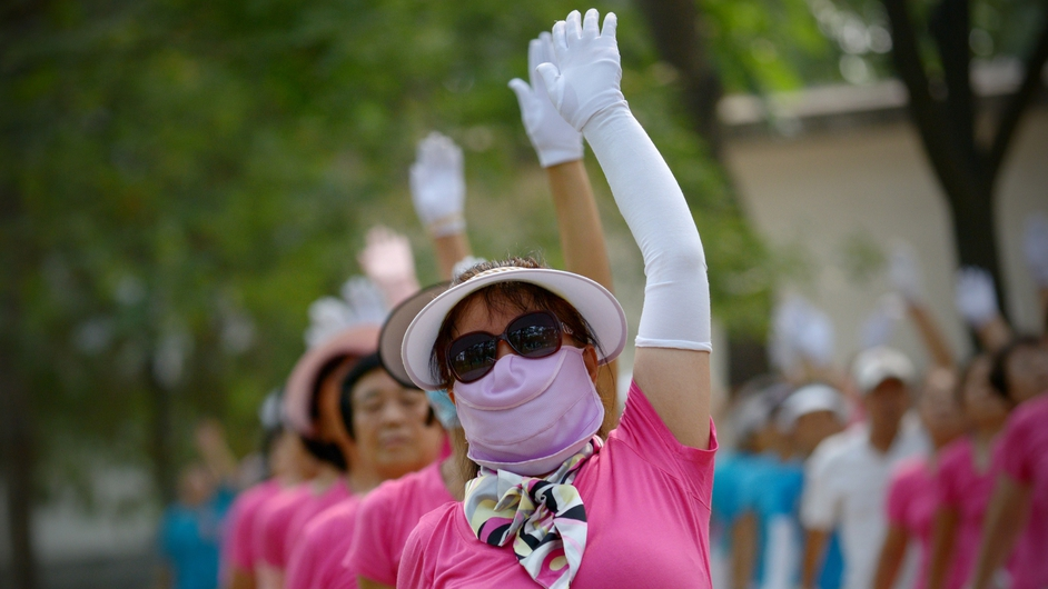 A woman wearing a face mask exercises at a park in Beijing