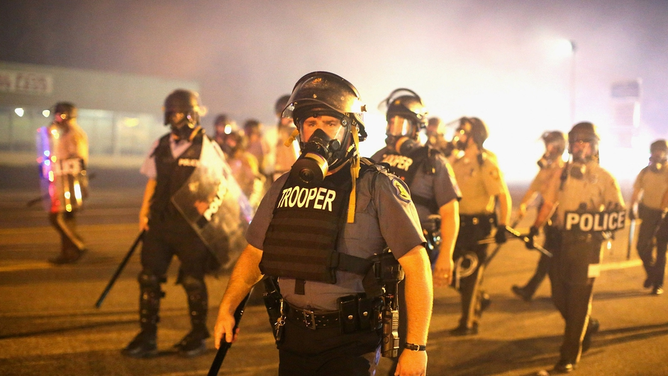 Police advance through a cloud of tear gas toward demonstrators protesting the killing of teenager Michael Brown in Ferguson, Missouri
