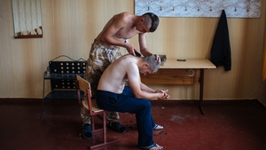 A Ukrainian activist has his hair cut by a comrade from Donbass Battalion at their camp based in a school in Popasnaya