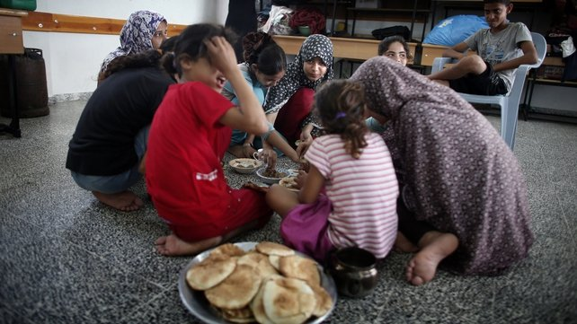 Palestinians share a breakfast at a UN school where families have sought refuge