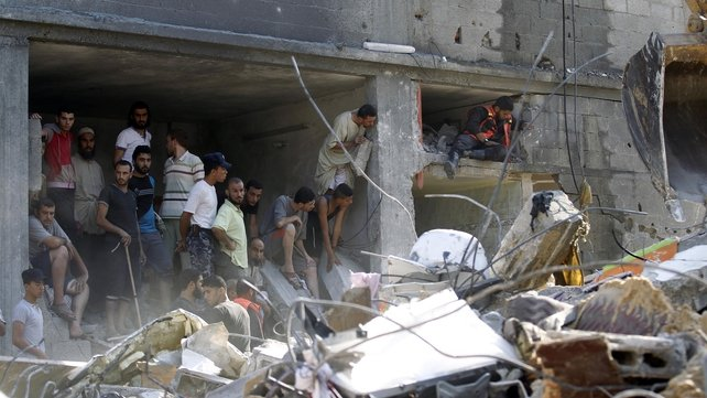 Palestinians gather around the rubble of a building destroyed following an Israeli military strike in Rafah