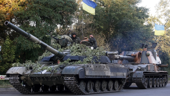 Ukrainian troops ride on a tank and a self-propelled gun near the eastern city of Luhansk