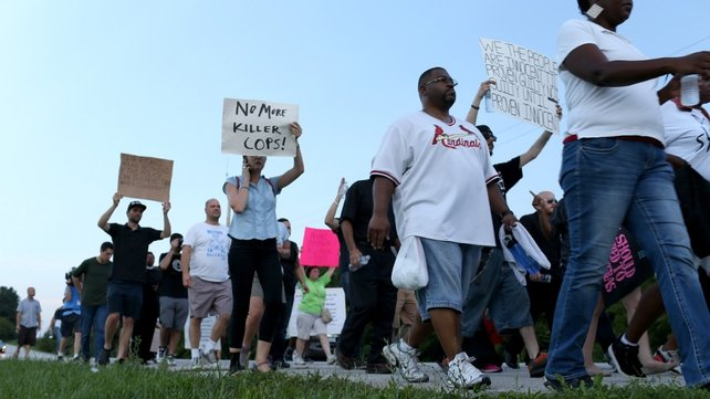 Demonstrators protesting the shooting death of Michael Brown march through the streets