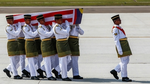 Royal Malay Regiment army personnel carry a coffin to a hearse during the arrival ceremony of Malaysia Airlines MH17 victims, at the Kuala Lumpur International airport in Sepang