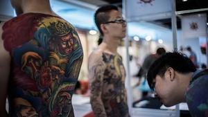 Men display their tattoos at the Hong Kong Tattoo Convention