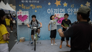 A child attempts to illuminate a set of lightbulbs using pedal power during an energy exhibition in Seoul