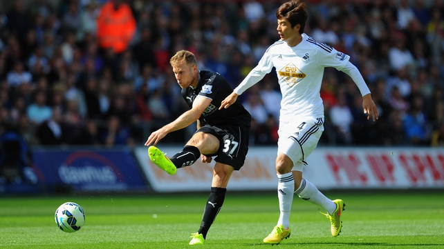 Burnley forward Scott Arfield gets in a shot at goal despite the attentions of Ki Sung-Yueng