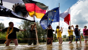 Activists hold banners and flags in the river Neisse to protest against the expansion of nearby open-pit coal mines
