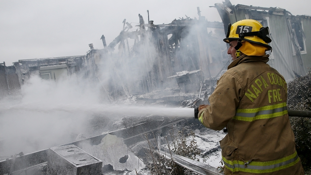 A Napa County firefighter sprays foam on hot spots from a fire at a mobile home park following the earthquake