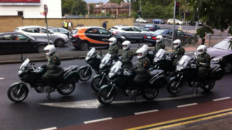 Army outriders wait to accompany the funeral cortege