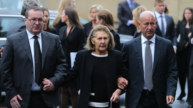 Kathleen Reynolds flanked by sons Albert (left) and Philip arrives for the funeral of her husband