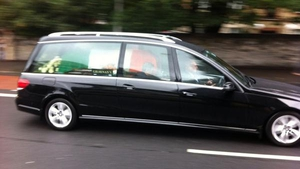The hearse carrying the former Taoiseach's remains departs for the  cemetery