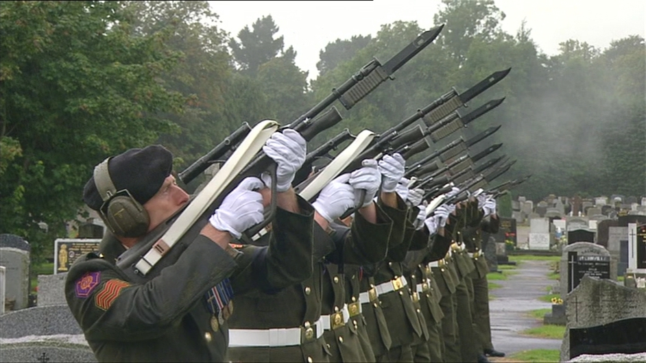 Members of the Defence Forces perform a salute at Mr Reynolds's graveside