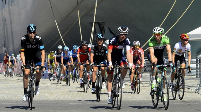 The pack rides past aircraft carrier Juan Carlos I at the Cadiz harbour at the start of the third stage