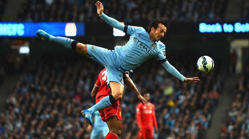 David Silva of Manchester City takes to the air during the Premier League match against Liverpool in Manchester