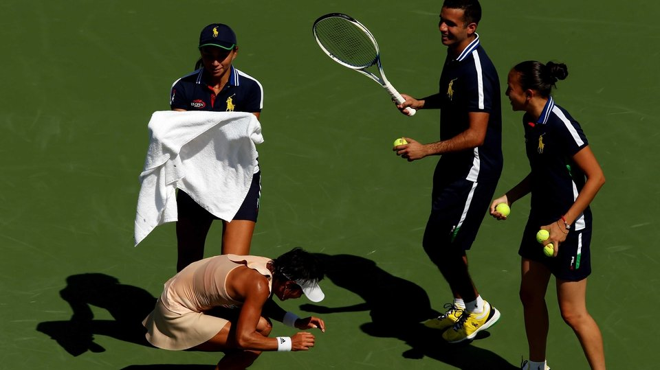 Ball people attempt to catch a honey bee in front of Kimiko Date-Krumm at the US Open, New York