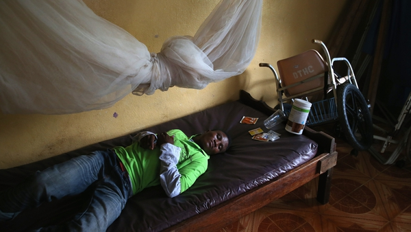 A man lies in an observation room at a government clinic in Dolo Town, Liberia