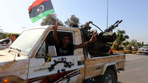 An Islamist fighter flashes the V sign for victory at the entrance of Tripoli international airport
