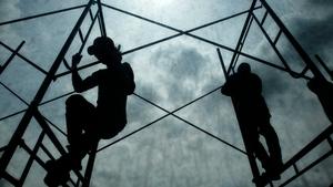 Men work on a building under construction in Bangkok, Thailand