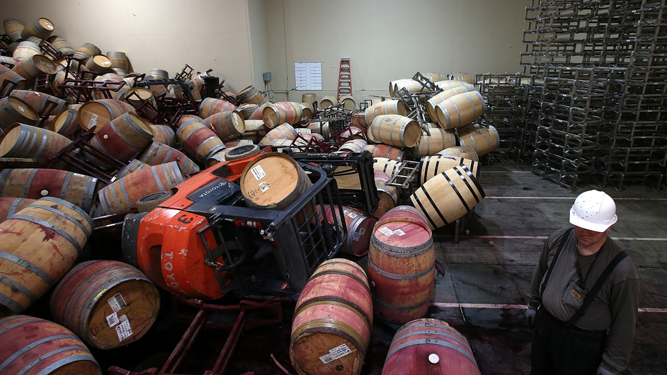 Cellar worker Adam Craig looks at a pile of wine barrels at a winery in Napa Valley following an earthquake in California