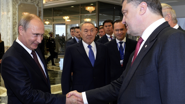 Vladimir Putin and Petro Poroshenko exchange a firm handshake before entering talks