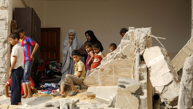 Palestinian women and children stand in a house destroyed by Israeli air strikes