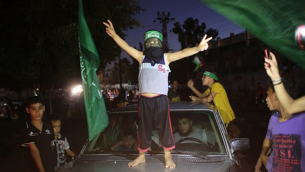 A Palestinian child wearing a Hamas headband celebrates the truce by flashing the victory sign in Rafah in Gaza