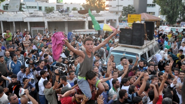 Palestinians gather in the streets to celebrate after a deal is reached