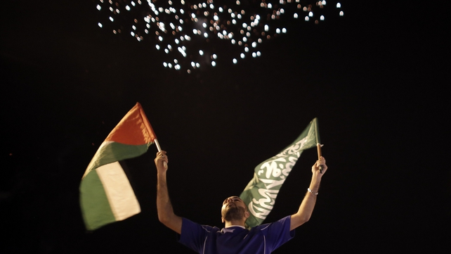 A man celebrates with a Palestinian flag and a Hamas flag