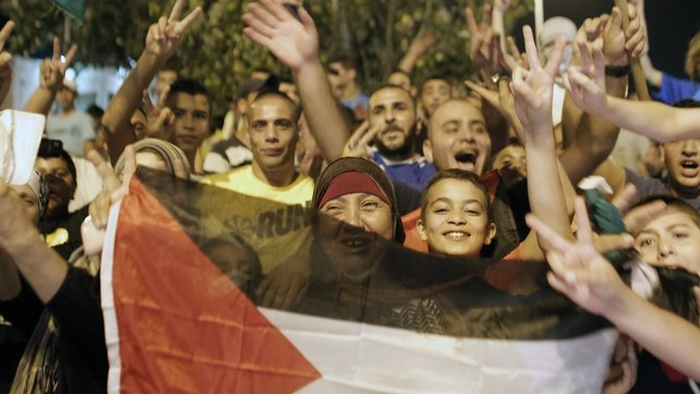 Palestinians wave a national flag as they celebrate in the streets in East Jerusalem
