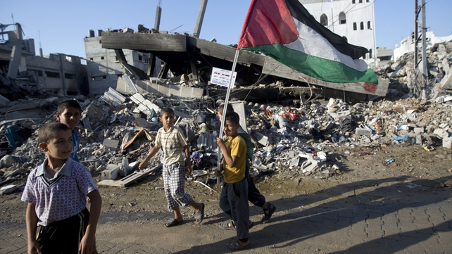 A group of Palestinian boys walk past destroyed houses in the Shejaiya neighbourhood of Gaza City