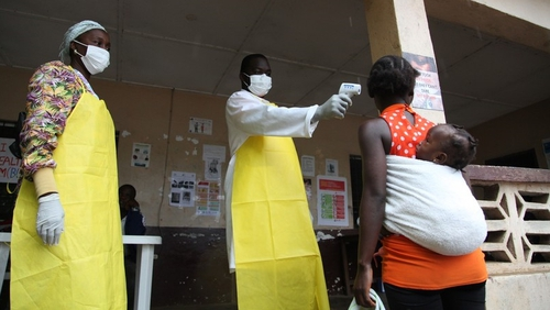 A Liberian nurse tests a woman's temperature as part of a drive to curb the spread of Ebola