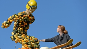 A woman looks at a ski jumper made out of hundreds of pumpkins on a farm in Klaistow, Germany